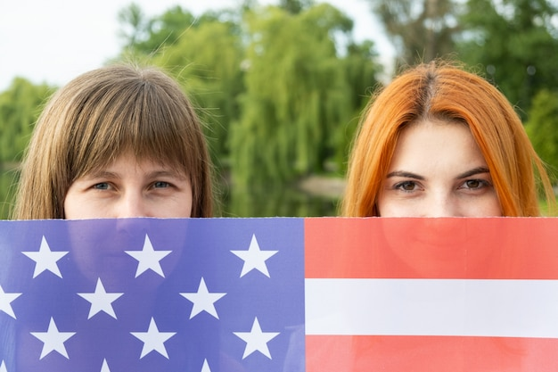 Портрет двух молодых женщин, скрывающих свои лица за национальным флагом сша