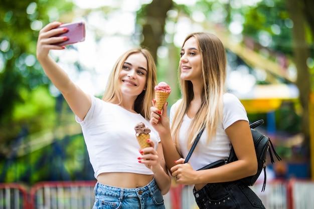 Портрет двух молодых женщин, стоящих вместе едят мороженое и принимая selfie в летней улице.