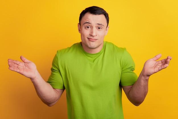 노란색 배경에 불확실한 우둔한 남자가 어깨를 으쓱하는 초상화
