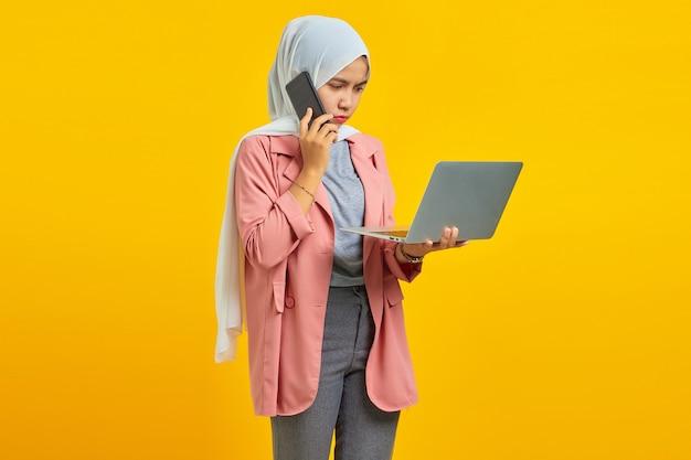 노란색 배경에 격리된 은색 노트북을 들고 스마트폰으로 말하는 불행한 아시아 여성의 초상화