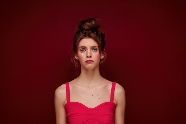 Портрет несчастной привлекательной молодой женщины с праздничным макияжем, с каштановыми волосами в пучке, с грустным лицом и сложенными губами, позирует с опущенными руками
