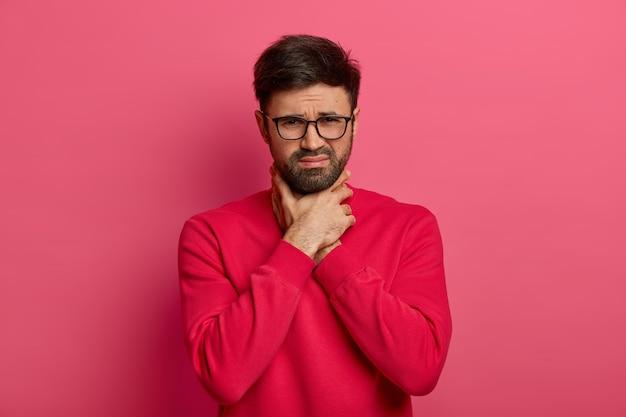 Портрет несчастного бородатого кавказца душит себя, не может дышать, задыхается и держит руки на шее, хмурится, болит горло и астматический припадок, позирует в помещении, небрежно одет