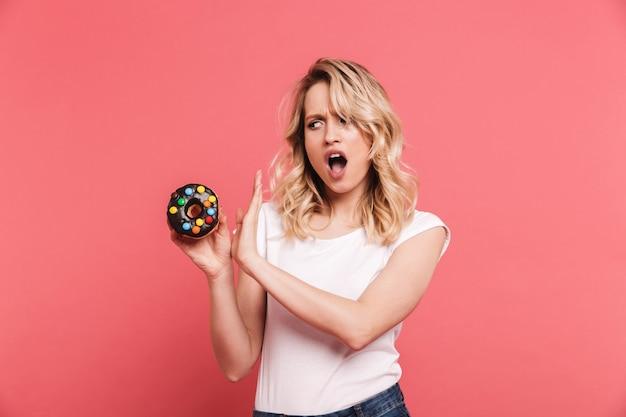 ピンクの壁に隔離されたおいしい甘いドーナツを保持しながら停止ジェスチャーをしているカジュアルなtシャツを着て不幸なブロンドの女性の肖像画
