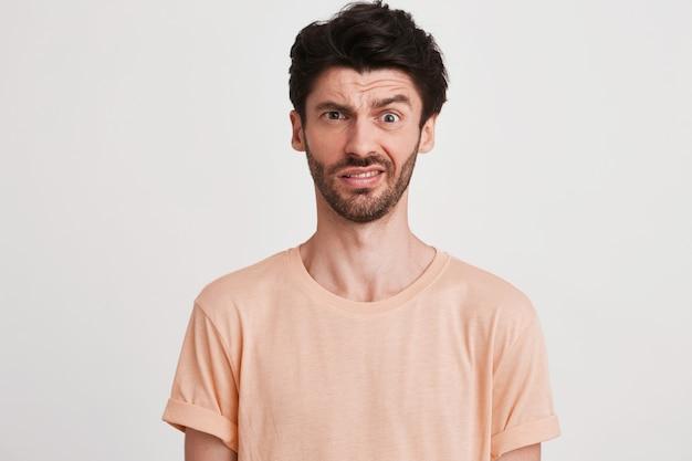 Портрет несчастного недовольного молодого человека с щетиной в персиковой футболке выглядит расстроенным и указывает в сторону пальцем, изолированным на белом
