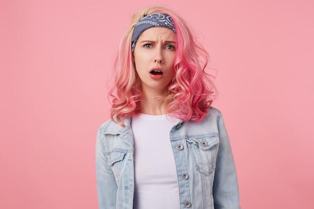 분홍색 머리를 가진 불행한 인상을 찌푸리고 귀여운 아가씨의 초상화, 입을 벌리고 서서 흰색 티셔츠와 데님 재킷을 입고 caera를보고.