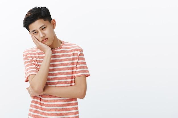 Портрет несчастного, одинокого и грустного молодого скучающего азиатского парня, положившего голову на ладонь, смотрящего расстроенным равнодушным взглядом, чувствуя себя неловко