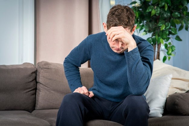 不幸な苦しみの落ち込んでいる男の肖像、若い欲求不満の悲しい動揺絶望的な男のソファのリビングルームに座って