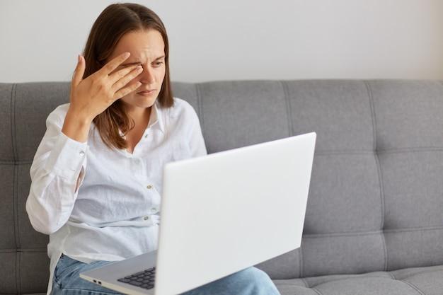 Портрет несчастной усталой женщины в белой рубашке и джинсах, сидящей на диване у себя дома, держащей ноутбук и смотрящей на экран компьютера, работая долгие часы, чувствует боль в глазах, глаза резины.