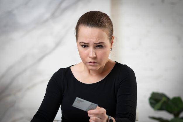 Портрет несчастной взволнованной злой грустной расстроенной девушки, молодой разочарованной разочарованной женщины, держащей кредит