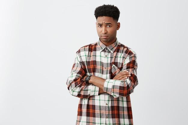 Портрет несчастного молодого привлекательного чернокожего человека с вьющимися волосами в повседневной клетчатой рубашке, скрещивающей руки с обиженным выражением после спора с подругой.