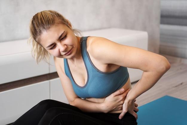 ヨガマットに座って、トレーニング後に彼女の背中に触れて、腰痛に苦しんで、痛みを感じて、側面図の不幸な若い女性の肖像画