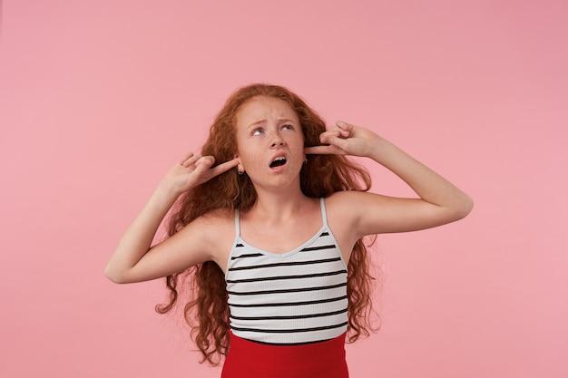Портрет недовольной кудрявой девушки с длинными рыжими волосами, смотрящей вверх с надутыми губами, закрывающей уши указательными пальцами и пытающейся избежать раздражающих звуков, позирует на розовом фоне
