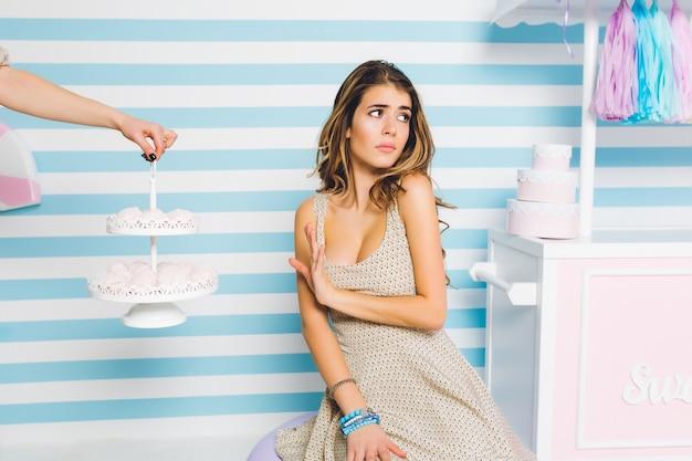 불쾌한 젊은 여자의 초상화는 귀여운 줄무늬 벽에 포즈를 취하는 맛있는 케이크를 멀리합니다. 세련된 드레스와 파란색 액세서리의 우아한 소녀는 달콤한 디저트를 먹고 손으로 서기를 거부합니다.