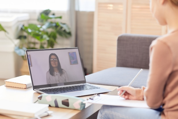 ノートパソコン、コピースペースを介して自宅で勉強しながらオンラインレッスンやオンラインクラスを見ている認識できない子供の肖像画