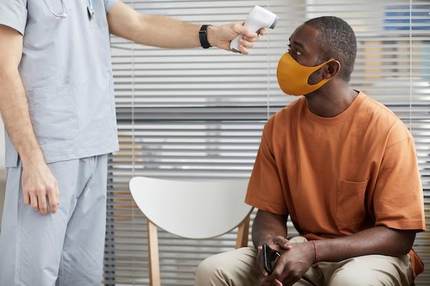 의료 클리닉에서 줄을 서서 기다리는 동안 마스크를 쓴 아프리카계 미국인 남성의 체온을 확인하는 알아볼 수 없는 남성 의사의 초상화