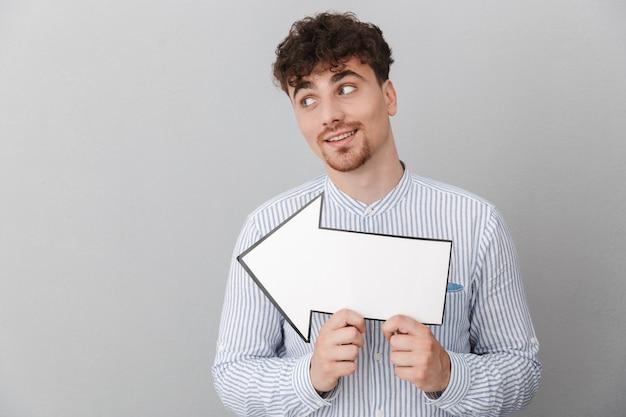 灰色の壁の上に分離された空白のコピースペース矢印ポインターを保持しているシャツに身を包んだ剃っていない美しい男の肖像画
