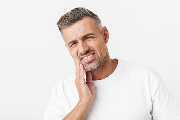 カジュアルなtシャツを着て頬に触れ、白で隔離された歯痛に苦しんでいる剛毛を持つ30代の剃っていない男の肖像画