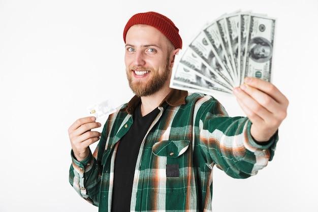 Портрет небритого мужчины, держащего кредитную карту и поклонника долларовых денег, стоя изолированно на белом фоне