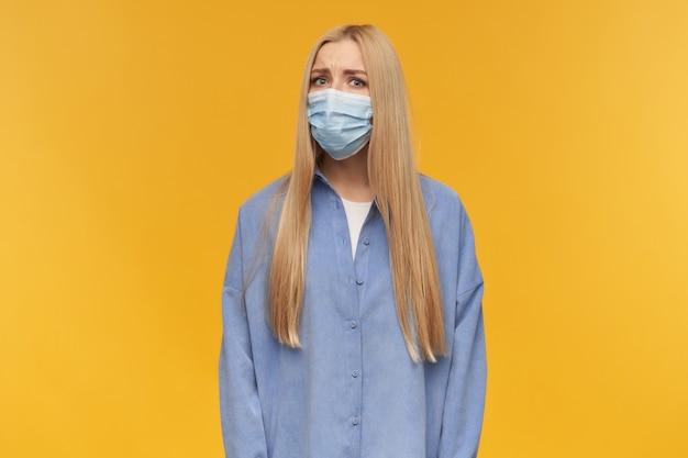 금발의 긴 머리를 가진 확실하지 않은 성인 여자의 초상화. 파란색 셔츠와 의료용 얼굴 마스크를 착용. 사람과 감정 개념. 오렌지 배경 위에 고립 된 카메라를 엄청나게보고