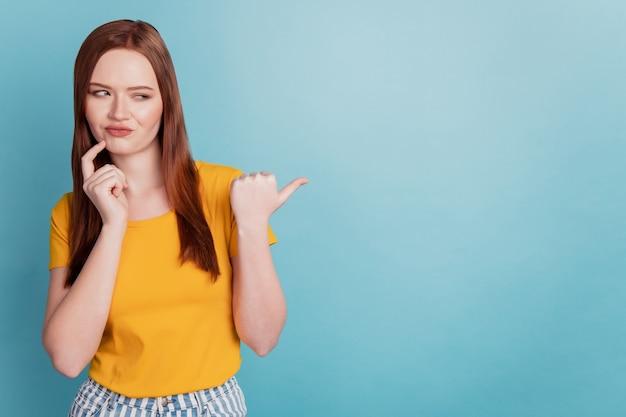 親指の空のスペースの指の頬を指している不確かな顧問の女性の肖像画は青い背景で考える