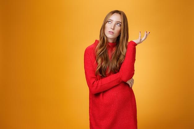 빨간색 스웨터를 입은 불확실한 생각을 하는 빨간 머리 여자친구의 초상화는 왼쪽 상단 모서리에 불확실한 표정을 짓고, 회상하고, 향수를 불러일으키고, 마음속으로 퍼즐을 풀고, 주황색 배경에 대해 포즈를 취합니다.