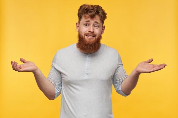 빨간 머리와 큰 수염을 가진 확신이없는 젊은 남성의 초상화는 손을 들고 노란색에 불확실한 표정으로 어깨를 으쓱합니다.