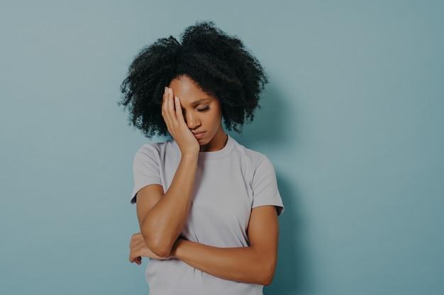 편두통이나 두통으로 고통받는 동안 스트레스를 받는 표정으로 머리를 손으로 잡고 캐주얼 옷을 입은 화가 난 아프리카 여성의 초상화. 좌절감을 느끼는 불행한 여성, 눈을 꼭 감고