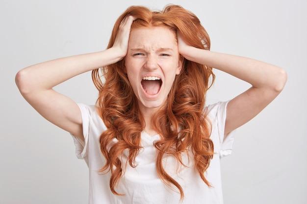 赤い波状の長い髪とそばかすがtシャツを着ている動揺して落ち込んでいる若い女性の肖像画は白い壁に孤立して心配と不幸を感じます