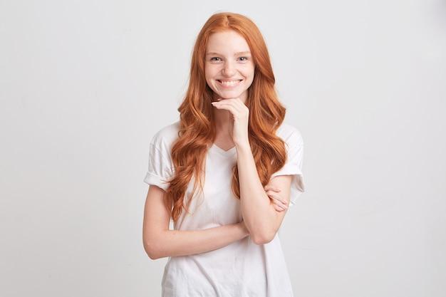 빨간색 물결 모양의 긴 머리와 주근깨가있는 화가 우울한 젊은 여성의 초상화는 흰 벽에 고립 된 걱정과 불행한 느낌의 티셔츠를 착용합니다.