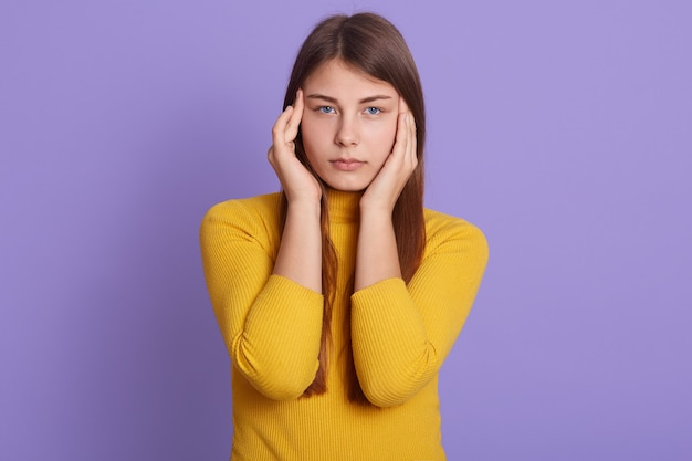 Портрет расстроенной измученной женщины страдает ужасной мигренью, массирует пальцами виски, чувствует боль, носит желтую повседневную рубашку, позирует в помещении, у сиреневой стены.