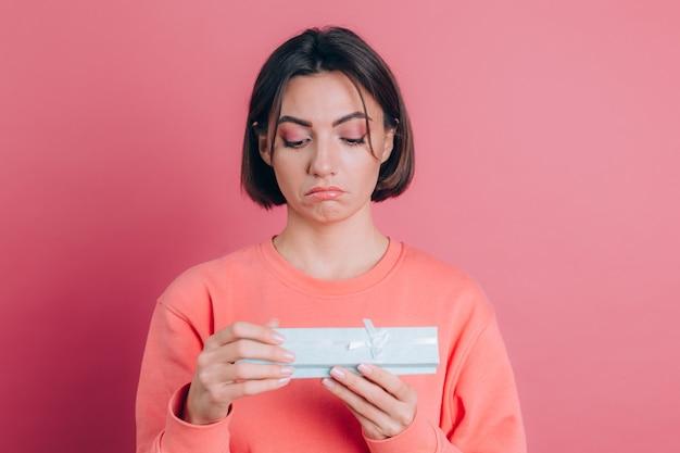분홍색 배경에 고립 된 선물 상자를 열고 화가 좌절 소녀의 초상화