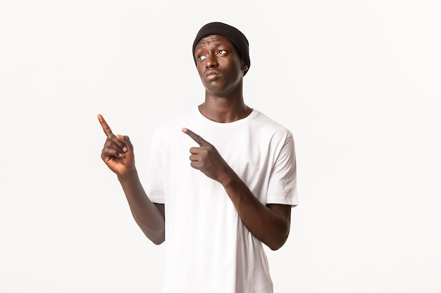 Портрет расстроенного мрачного афро-американского парня в шапочке, грустно надувшись, указывая пальцами в верхнем левом углу, что-то разочаровывает