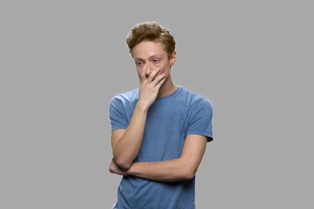 灰色の背景に対して動揺した10代の少年の肖像画。物思いにふける若い悲しいティーンエイジャーの男。間違いが心配。
