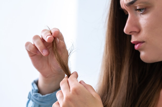 乾燥した髪と枝毛に苦しんでいる髪の損傷したロックと動揺して不幸な悲しい女性の肖像画。