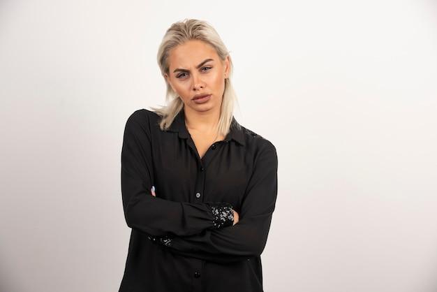 白い背景にポーズをとって黒いシャツを着て動揺した女性の肖像画。高品質の写真