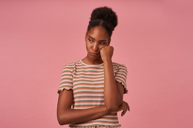 분홍색 벽 위에 절연 슬프게도 옆으로 보면서 제기 손에 그녀의 뺨을 기대어 화가 젊은 갈색 머리 곱슬 여성의 초상화