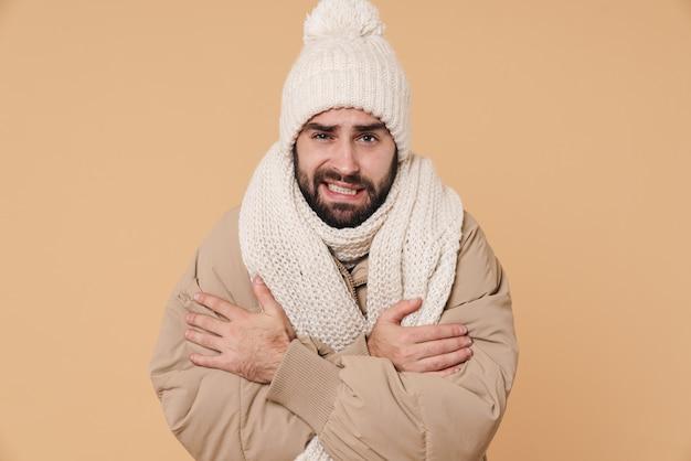 Портрет расстроенного молодого человека в зимней одежде, дрожащего от холода, изолированного на бежевом