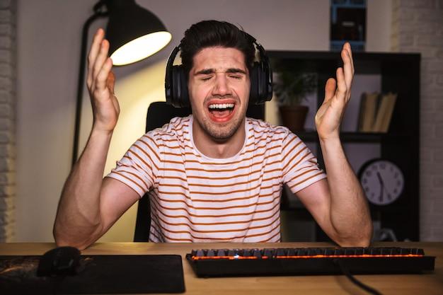 Портрет расстроенного молодого человека в гарнитуре, кричащего, сидя за столом с компьютером в комнате и смотрящего на камеру
