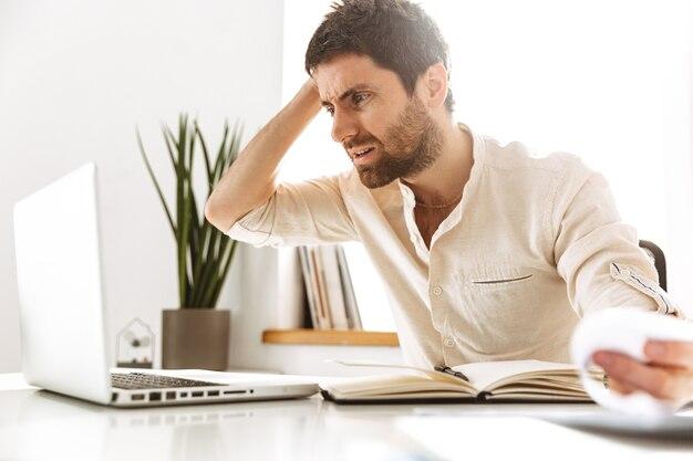 Портрет встревоженного бизнесмена 30-х годов в белой рубашке, работающего с ноутбуком и бумажными документами, сидя в ярком офисе