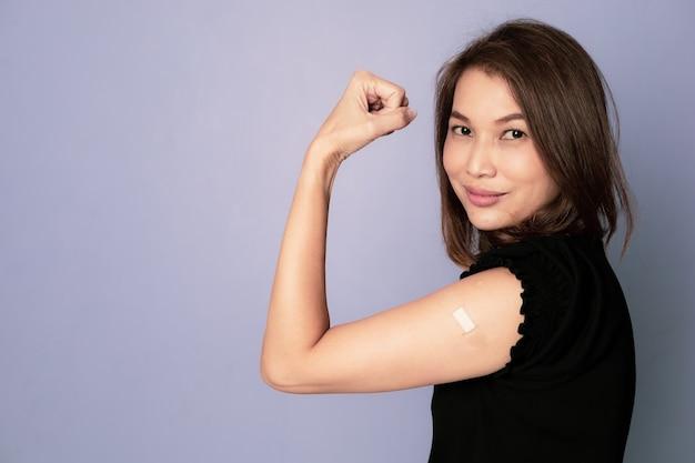 腕に絆創膏バンドの援助を示し、コロナウイルスワクチン注射がカメラを見た後の勝利と信頼のサインで拳パンチを示すワクチン接種されたアジアの女性の肖像画。予防接種の概念を取得します。