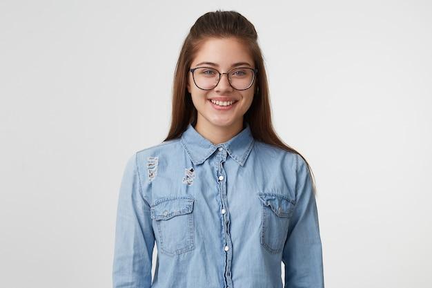 Портрет очень милой и привлекательной женщины в очках, улыбающейся, одетой в модную джинсовую рубашку