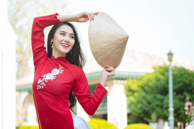 ベトナムの女の子の伝統的な赤いドレスの肖像画、ベトナムを身に着けている美しい若いアジアの女性