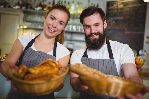 Портрет официанта и официантка, проведение корзины хлеба