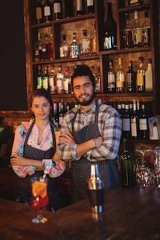 Портрет официанта и официантки, стоящих со скрещенными руками за стойкой