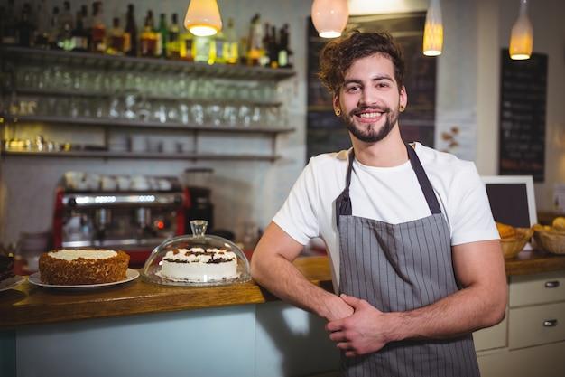 Портрет официант стоял у прилавка