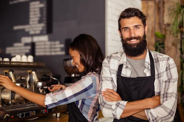 Портрет официанта, стоя со скрещенными руками, в то время как официантка работает в фоновом режиме