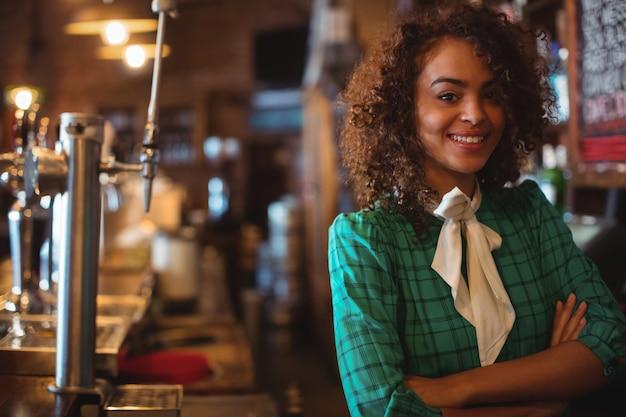 Портрет официантки, стоящей со скрещенными руками за стойкой