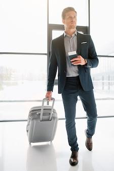 Портрет идущего молодого бизнесмена, идущего в зале аэропорта