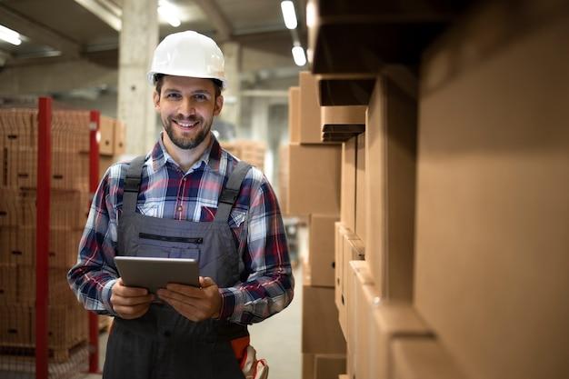 タブレットコンピューターを保持し、工場の保管室で商品と段ボール箱のそばに立っている倉庫監督者の肖像画。