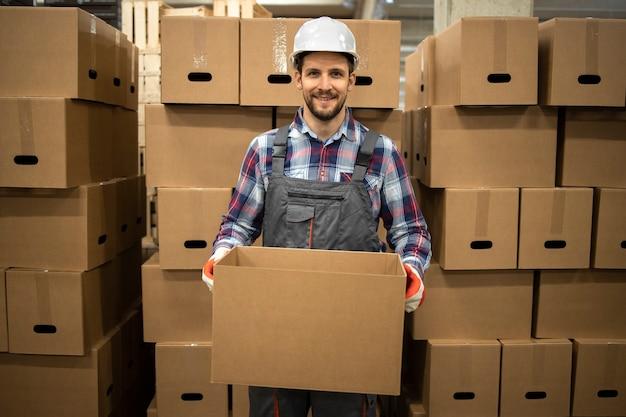 작업복 및 공장 저장소에 물건을 재배치하는 골판지 상자를 들고 hardhat에서 창고 노동자의 초상화.